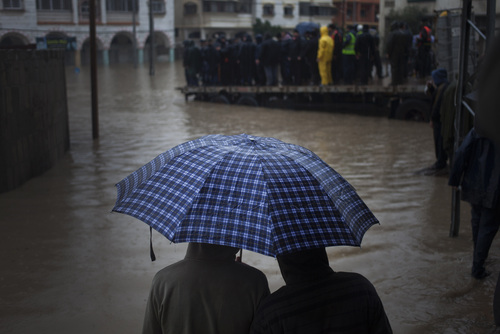 A couple of Palestinian people watch rescue members evacuate residents following heavy rains in Gaza City, Saturday, Dec. 14, 2013. Rescue workers evacuated more than 5,000 Gaza Strip residents from homes flooded by four days of heavy rain, using fishing boats and heavy construction equipment to pluck some of those trapped from upper floors, an official said Saturday. (AP Photo/Khalil Hamra)