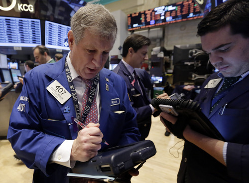 Richard Newman, left, works with fellow traders on the floor of the New York Stock Exchange Monday, Dec. 16, 2013. The stock market is opening sharply higher after a pair of multibillion-dollar deals and signs of strength in U.S. manufacturing. (AP Photo/Richard Drew)