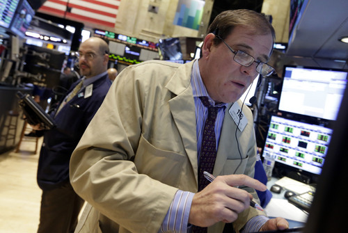 Trader Jonathan Niles, right, works on the floor of the New York Stock Exchange Monday, Dec. 16, 2013. U.S. stocks rose sharply on Monday, powered by two big corporate deals and news that suggests the economy is getting stronger.  (AP Photo/Richard Drew)
