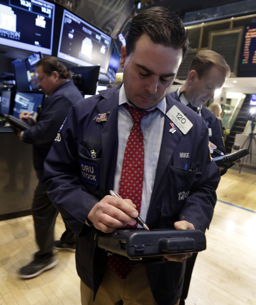 Trader Michael Iozzi, center, works on the floor of the New York Stock Exchange Monday, Dec. 16, 2013. U.S. stocks rose sharply on Monday, powered by two big corporate deals and news that suggests the economy is getting stronger.  (AP Photo/Richard Drew)