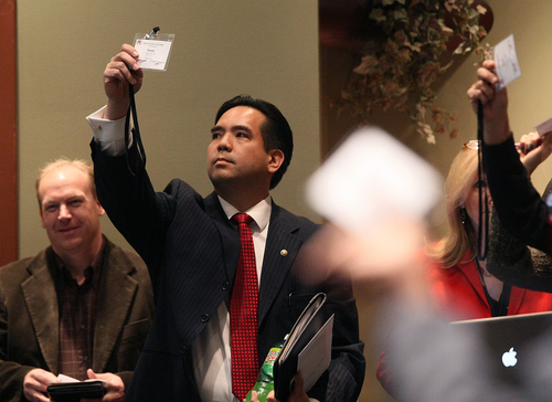 Sean Reyes raises his badge as he votes on a parliamentary rule Saturday, Dec. 14, 2013, as the Republican State Central Committee met to choose three names to send to the governor to replace former attorney general John Swallow. After five ballots they selected: Sean Reyes, Robert Smith, and finally Brian Tarbet.  (AP Photo/ The Salt Lake Tribune, Scott Sommerdorf)