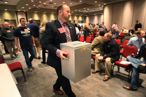 One of the voting boxes is removed after voting was cut off Saturday, Dec. 14, 2013, as the Republican State Central Committee met to choose three names to send to the governor to replace former attorney general John Swallow. After five ballots they selected: Sean Reyes, Robert Smith, and finally Brian Tarbet.  (AP Photo/ The Salt Lake Tribune, Scott Sommerdorf)
