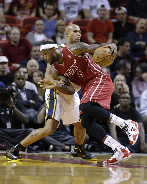 Miami Heat's LeBron James (6) drives to the basket past Utah Jazz's Richard Jefferson in the first half of an NBA basketball game, Monday, Dec. 16, 2013, in Miami. (AP Photo/Lynne Sladky)