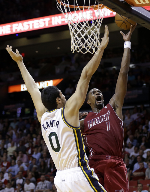 Miami Heat's Chris Bosh (1) is fouled by Utah Jazz's Enes Kanter (0) as he shoots in the second half of an NBA basketball game, Monday, Dec. 16, 2013, in Miami. The Heat defeated the Jazz 117-94. (AP Photo/Lynne Sladky)