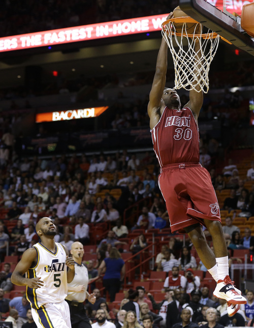 Miami Heat's Norris Cole (30) dunks over Utah Jazz's John Lucas III (5) in the second half of an NBA basketball game, Monday, Dec. 16, 2013, in Miami. The Heat defeated the Jazz 117-94. (AP Photo/Lynne Sladky)
