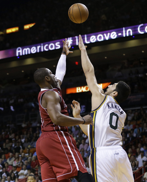 Miami Heat's Dwyane Wade, left, shoots over Utah Jazz's Enes Kanter (0) in the second half of an NBA basketball game, Monday, Dec. 16, 2013, in Miami. The Heat defeated the Jazz 117-94. (AP Photo/Lynne Sladky)