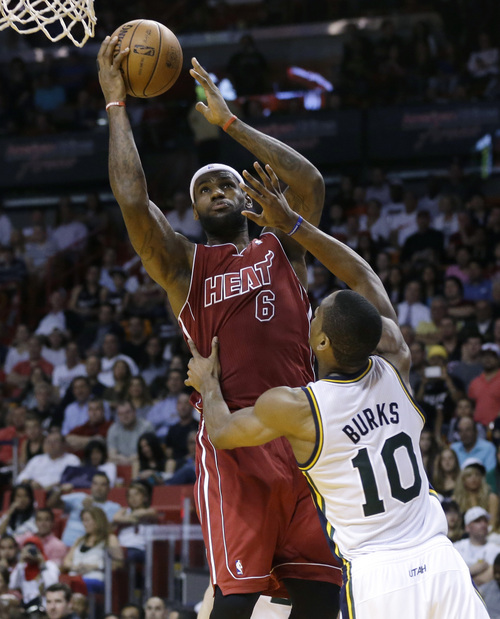 Miami Heat's LeBron James (6) shoots as Utah Jazz's Alec Burks (10) defends in the second half of an NBA basketball game, Monday, Dec. 16, 2013, in Miami. The Heat defeated the Jazz 117-94. (AP Photo/Lynne Sladky)