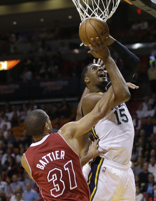 Utah Jazz's Derrick Favors (15) is fouled by Miami Heat's Shane Battier (31) in the first half of an NBA basketball game, Monday, Dec. 16, 2013, in Miami. (AP Photo/Lynne Sladky)