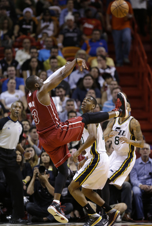 Miami Heat's Dwyane Wade (3) shoots over Utah Jazz's Alec Burks, center, in the first half of an NBA basketball game, Monday, Dec. 16, 2013, in Miami. (AP Photo/Lynne Sladky)