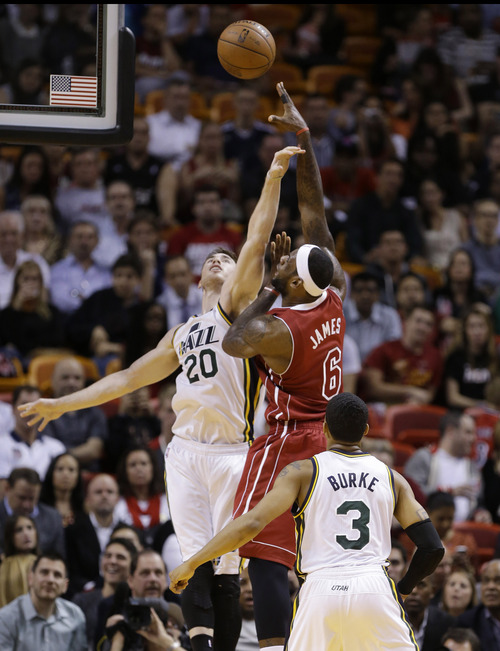 Miami Heat's LeBron James (6) is fouled by Utah Jazz's Gordon Hayward (20) in the first half of an NBA basketball game, Monday, Dec. 16, 2013, in Miami. At right is Trey Burke (3). (AP Photo/Lynne Sladky)