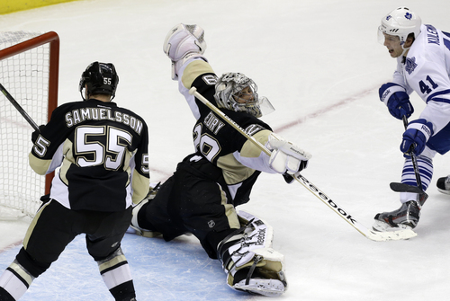 Pittsburgh Penguins goalie Marc-Andre Fleury (29) stops a shot by Toronto Maple Leafs' Nikolai Kulemin (41) in the third period of an NHL hockey game in Pittsburgh, Monday, Dec. 16, 2013. The Penguins won 3-1. (AP Photo/Gene J. Puskar)
