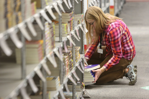 Francisco Kjolseth  |  The Salt Lake Tribune As the cost of books rises, a University of Utah Academic Senate committee is looking at reducing costs by using free online textbooks. On Monday, Dec. 9, 2013, U. student Paige Westenskow begins filling the racks at the University of Utah campus bookstore in anticipation of the Spring semester.