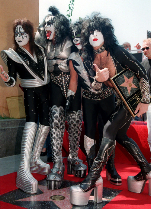 FILE - In this Aug. 11, 1999 file photo, Kiss band members, from left, Ace Frehley, Gene Simmons, Peter Criss and Paul Stanley take the ceremonial first step on their new star on the Hollywood Walk of Fame in Los Angeles. Kiss will be inducted into the 2014 Rock and Roll Hall of Fame on April 10, 2014 at the Barclays Center in New York. (AP Photo/Katie Callan, File)