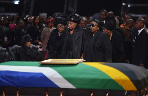 Winnie Madikizela-Mandela, left, Nelson Mandela's former wife, left and Nelson Mandela's widow Graca Machel stand over  the former South African president's casket during his funeral service in Qunu, South Africa, Sunday, December 15, 2013. The woman on the right is unidentified. (AP Photo/Odd Andersen, Pool)