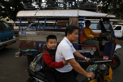 In this Thursday, Dec. 12, 2013, photo, a Lao boy holds his father as he goes to school on a scooter, in the capital Vientiane, Laos.  The kidnapping of Sombath Somphone, the country's leading civil rights activist, has revealed the one-party communist Laos, one of the five such regimes in the world, as one of Asia's most repressive societies. Yet, the country has maintained an image among tourists as a laid-back country of smiles. (AP Photo /Manish Swarup)