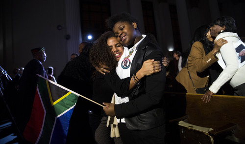 Sydney Orr, left, and Snovuyo Dingwayo, right, embrace after a memorial service for former South African President Nelson Mandela at the Rainbow PUSH headquarters on Friday, Dec. 13, 2013, in Chicago. (AP Photo/Andrew A. Nelles)