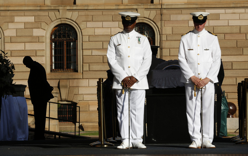 Mandla Mandela, the oldest grandson of former South African President Nelson Mandela is silhouetted as he looks down beside his grandfather's casket on the third and final day of lying in state at the Union Buildings in Pretoria, South Africa, Friday, Dec. 13, 2013. (AP Photo/Matt Dunham, Pool)