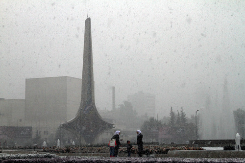 People play in the snow in Damascus, Syria, Friday, Dec. 13, 2013 as a blustery storm, dubbed Alexa, brought gusty winds, torrential rains and heavy snowfall to most parts of Syria and the entire Middle East. The snow has heaped another layer of misery on the already grim existence of many of the more than 2 million Syrians who have fled the civil war raging in their homeland.(AP Photo)