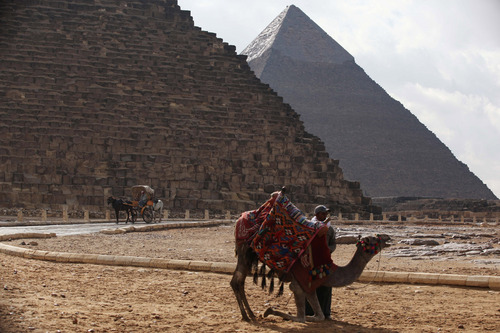 A man makes his camel sit at the historical site of the Giza Pyramids near Cairo, Egypt, on Friday, Dec. 13, 2013. Tourism in Egypt has dropped following unrest surrounding the July 3 popularly backed military coup that ousted President Mohammed Morsi. (AP Photo/Jon Gambrell)