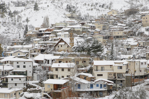 A view of the snowy Palaichori village after three days of heavy snowfall on the Troodos Mountain,  Friday, Dec. 13 2013. Almost 40 mountain villages remain cut off due to heavy snowfall, while all roads leading to the peak of the island's Troodos mountain range remains closed for all vehicles. Power outages in some areas has been restored, Cyprus Electricity Authority spokesman Costas Gavrielides said. The cold spell hit the island midweek and brought lots of snow in mountainous areas as temperatures dropped some 11 degrees Celsius lower than seasonal norms. Conditions are forecast to improve over the weekend. (AP Photo/Petros Karadjias)