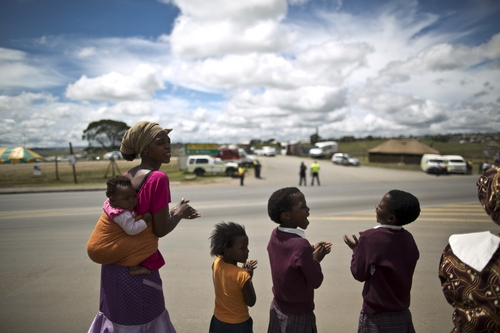 South Africans wait the motorcade transporting the body of Former President Nelson Mandela to pass by, in the town of Mthatha on its way to Qunu, South Africa Saturday, Dec. 14, 2013. (AP Photo/Muhammed Muheisen)
