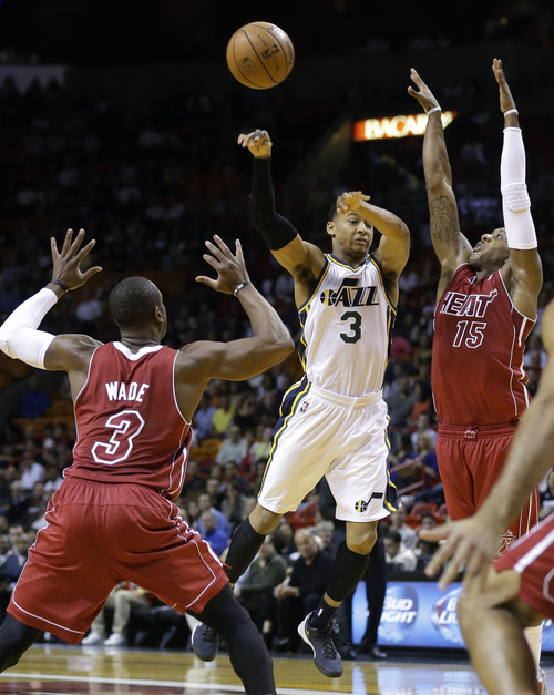 Utah Jazz's Trey Burke (3) passes the ball as Miami Heat's Dwyane Wade (3) and Mario Chalmers (15) defend in the first half of an NBA basketball game, Monday, Dec. 16, 2013, in Miami. (AP Photo/Lynne Sladky)