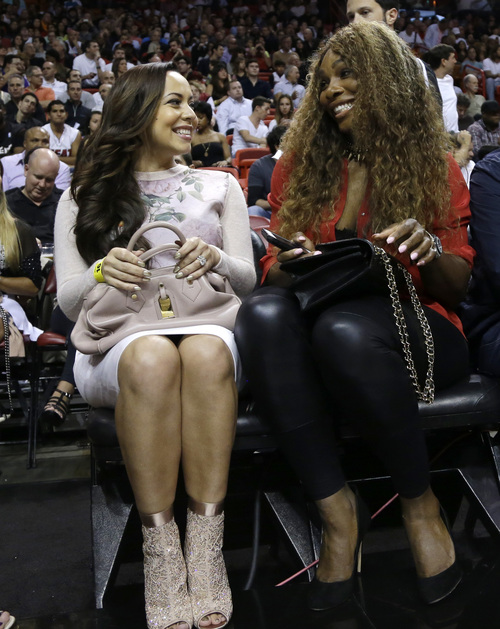 Adrienne Bosh, the wife of Miami Heat center Chris Bosh, left, sits with tennis player Serena Williams, right, during an NBA basketball game between the Miami Heat and Utah Jazz, Monday, Dec. 16, 2013, in Miami. (AP Photo/Lynne Sladky)
