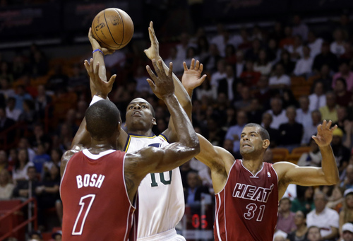 Utah Jazz's Alec Burks (10) attempts a shot as Miami Heat's Chris Bosh (1) and Shane Battier (31) defend in the first half of an NBA basketball game, Monday, Dec. 16, 2013, in Miami. (AP Photo/Lynne Sladky)