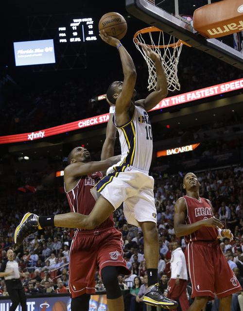 Utah Jazz's Alec Burks (10) shoots over Miami Heat's Chris Bosh, left, and Ray Allen, right, in the first half of an NBA basketball game, Monday, Dec. 16, 2013, in Miami. (AP Photo/Lynne Sladky)