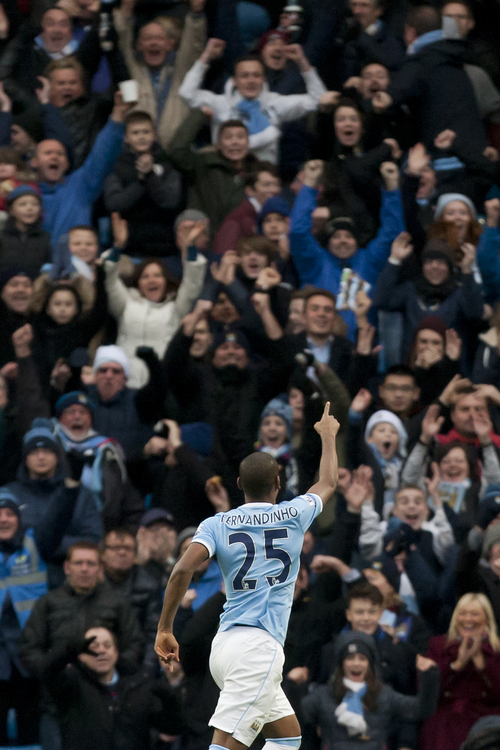 Manchester City's Fernandinho celebrates after scoring against Arsenal during their English Premier League soccer match at the Etihad Stadium, Manchester, England, Saturday Dec. 14, 2013. (AP Photo/Jon Super)