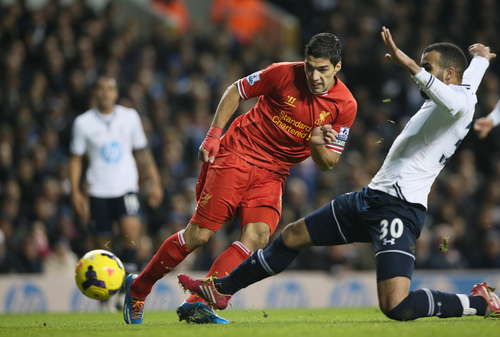Liverpool's Luis Suarez, left, shoots and scores the opening goal during their English Premier League soccer match between Tottenham Hotspur and Liverpool at the White Hart Lane stadium in London Sunday, Dec. 15,  2013. (AP Photo/Alastair Grant)