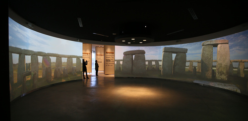 Visitors look at the audio-visual exhibits at Stonehenge, England, Tuesday, Dec. 17, 2013. It has been standing for thousands of years, so Britain's ancient Stonehenge monument was due a makeover. The 27 million pound ($44 million) renovation which was previewed Tuesday includes a new building 1.5 miles (2.4 kilometers) from the stones where the 1 million a year visitors can watch an exhibition about Neolithic life. (AP Photo/Alastair Grant)