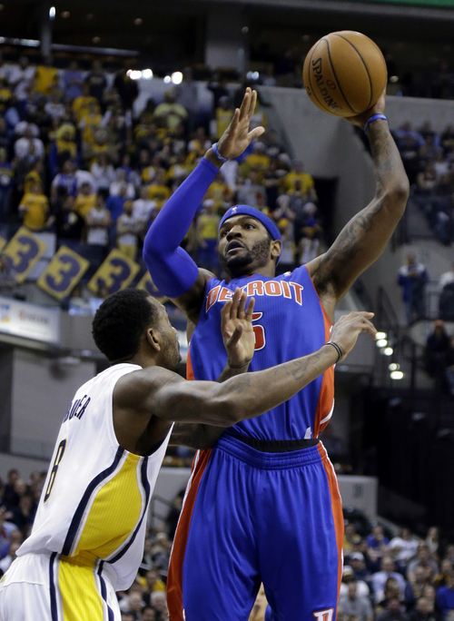 Detroit Pistons forward Josh Smith, right, shoots over Indiana Pacers guard Rasual Butler in the first half of an NBA basketball game in Indianapolis, Monday, Dec. 16, 2013.  (AP Photo/Michael Conroy)