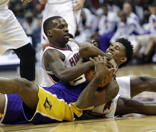 Los Angeles Lakers forward Nick Young (0) and Atlanta Hawks guard Shelvin Mack (8) scramble for the loose ball in the second half of an NBA basketball game, Monday, Dec. 16, 2013, in Atlanta. The Hawks won 114-100. (AP Photo/John Bazemore)