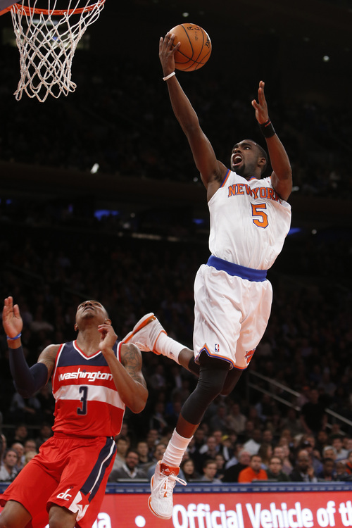 New York Knicks' Tim Hardaway Jr. (5) goes to the basket against Washington Wizards' Bradley Beal (3) during the first half of an NBA basketball game Monday, Dec. 16, 2013, in New York. (AP Photo/Jason DeCrow)