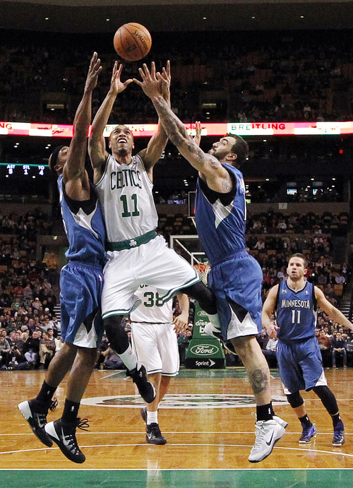 Boston Celtics' Courtney Lee (11) drives for the basket between Minnesota Timberwolves' Dante Cunningham, left, and Nikola Pekovic in the second quarter of an NBA basketball game in Boston, Monday, Dec. 16, 2013. (AP Photo/Michael Dwyer)
