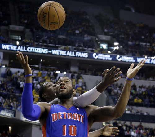 Indiana Pacers center Ian Mahinmi, back, comes from behind to knock the ball away from Detroit Pistons forward Greg Monroe in the first half of an NBA basketball game in Indianapolis, Monday, Dec. 16, 2013.  (AP Photo/Michael Conroy)