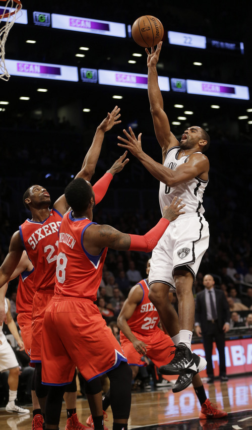 Brooklyn Nets' Alan Anderson, right, sinks a basket and draws a foul while Philadelphia 76ers' Thaddeus Young, left, and Tony Wroten (8) defend during the first half of the NBA basketball game at the Barclays Center, Monday, Dec. 16, 2013, in New York.  (AP Photo/Seth Wenig)