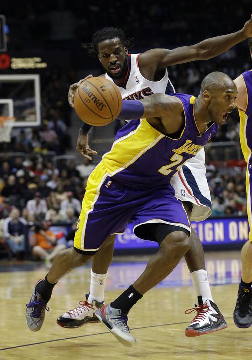 Los Angeles Lakers guard Kobe Bryant (24) drives past Atlanta Hawks forward DeMarre Carroll (5) in the second half of an NBA basketball game, Monday, Dec. 16, 2013, in Atlanta. The Hawks won 114-100. (AP Photo/John Bazemore)