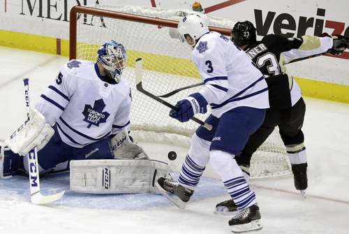 Pittsburgh Penguins right wing Chris Conner (23) gets the puck behind Toronto Maple Leafs goalie Jonathan Bernier (45) and Dion Phaneuf (3) for a goal in the first period of an NHL hockey game, Monday, Dec. 16, 2013, in Pittsburgh. (AP Photo/Gene J. Puskar)