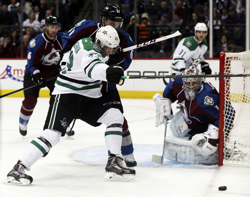 Dallas Stars right wing Valeri Nichushkin, front left, of Russia, battles to take a shot as Colorado Avalanche defenseman Andre Benoit, back left, covers and goalie Semyon Varlamov, of Russia, protects the net in the first period of an NHL hockey game in Denver on Monday, Dec. 16, 2013. (AP Photo/David Zalubowski)