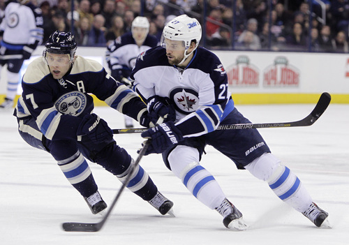 Winnipeg Jets' Eric Tangradi, right, carries the puck across the blue line as Columbus Blue Jackets' Jack Johnson defends during the first period of an NHL hockey game Monday, Dec. 16, 2013, in Columbus, Ohio. (AP Photo/Jay LaPrete)