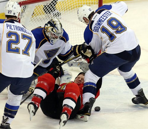 Ottawa Senators Chris Neil (25) is checked by St. Louis Blues Jay Bouwmeester (19) as Blues goaltender Brian Elliot (1) looks for the puck during first period, NHL hockey between the Ottawa Senators and the St Louis Blues in Ottawa Monday,  Dec. 16, 2013. (AP Photo/The Canadian Press, Fred Chartrand)