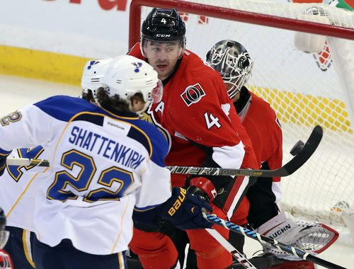 Ottawa Senators Chris Phillips (4) and goaltender Robin lehner (40) look on as St.Louis Blues Kevin Shattenkirk (22) attempts to handle a flying puck during first period NHL hockey action in Ottawa Monday, Dec. 16, 2013. (AP Photo/The Canadian Press, Fred Chartrand)