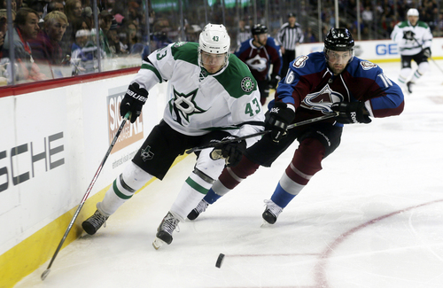 Dallas Stars right wing Valeri Nichushkin, left, of Russia, pursues the puck with Colorado Avalanche defenseman Cory Sarich in the third period of the Avalanche's 6-2 victory in an NHL hockey game in Denver on Monday, Dec. 16, 2013. (AP Photo/David Zalubowski)