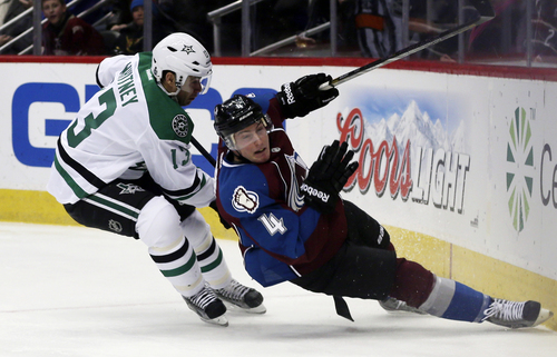 Colorado Avalanche defenseman Tyson Barrie, right, slides into the boards as Dallas Stars left wing Ray Whitney covers in the third period of the Avalanche's 6-2 victory in an NHL hockey game in Denver on Monday, Dec. 16, 2013. (AP Photo/David Zalubowski)