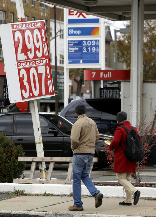 People walk toward the intersection of State Highway 139 and John F. Kennedy Boulevard in Jersey City, N.J., where a Lukoil gas station advertises gas for $2.99, Tuesday, Nov. 12, 2013. A nearby Exxon station is advertising at $3.09. Analysts say the falling prices are mostly due to less expensive seasonal gasoline and crude oil prices falling below $100 per barrel. (AP Photo/Julio Cortez)