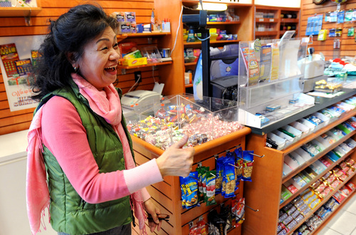 Owner Young Soo Lee basks in the attention at her small Alliance Center office bulding newsstand on Wednesday, Dec. 18, 2013, in Atlanta, after lottery officials said one of two winning Mega Millions lottery tickets were purchased from her store in Tuesday's $636 million drawing,  The store owner said she sold 1300 lottery tickets on Tuesday rather than the normal sales of about 100 tickets. (AP Photo/David Tulis)