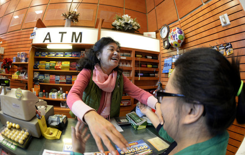 In this photo taken with a fisheye lens, newsstand owner Young Soo Lee, left, is congratulated by customer Szu Ho at her small Alliance Center office bulding newsstand on Wednesday, Dec. 18, 2013, in Atlanta, after lottery officials said one of two winning Mega Millions lottery tickets were purchased from her store in Tuesday's $636 million drawing,  The store owner said she sold 1300 lottery tickets on Tuesday rather than the normal sales of about 100 tickets. (AP Photo/David Tulis)