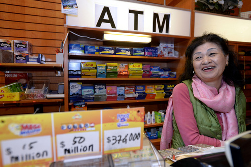 CORRECTS SPELLING OF NAME TO YOUNG SOO LEE, NOT YOUNG SOOLEE - Owner Young Soo Lee basks in the attention at her small Alliance Center office bulding newsstand on Wednesday, Dec. 18, 2013, in Atlanta, after lottery officials said one of two winning Mega Millions lottery tickets were purchased from her store in Tuesday's $636 million drawing,  The store owner said she sold 1300 lottery tickets on Tuesday rather than the normal sales of about 100 tickets. (AP Photo/David Tulis)